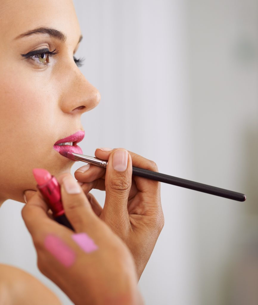 Cropped shot of a beautiful woman having lipstick applied with a makeup brush