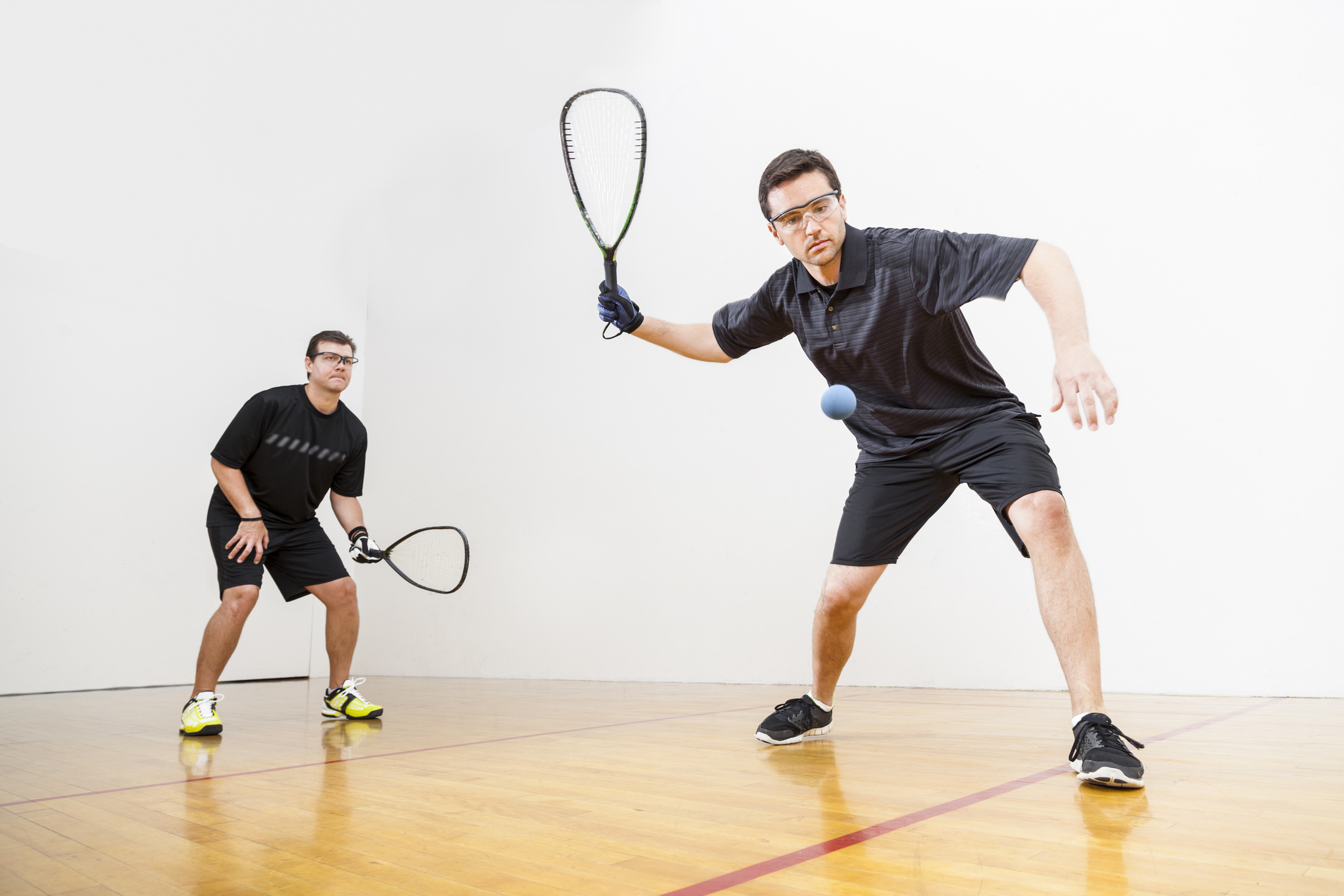 Two men playing racquetball on court.